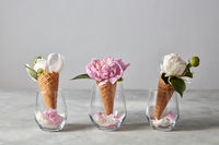 Wafer cones for ice cream with flowers peony and petals in a glasses on a gray table.