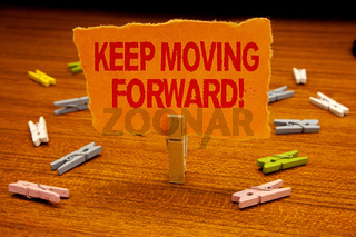 Writing note showing  Keep Moving Forward Motivational Call. Business photo showcasing Optimism Progress Persevere Move Paperclip holding orange page show red text woody floor with clip.