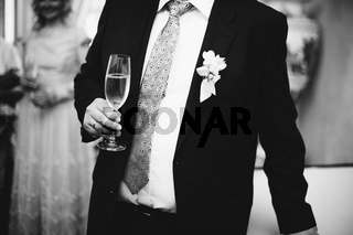 Closeup image of black and white half length body portrait of man wear a tuxedo and holds champagne on the wedding party background