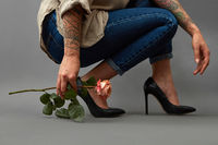 Girl with a tattoo in jeans, and black heeled shoes, squatting and holding a fresh pink flower around a dark background with space for text. Card