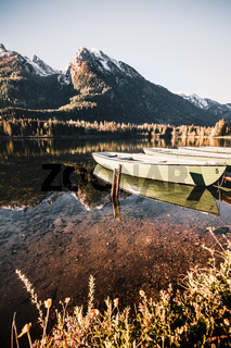 Colorful summer sunrise on the Hintersee lake with white pleasure launches.