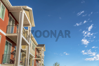 House exterior with small balconies and combination of white and orange wall