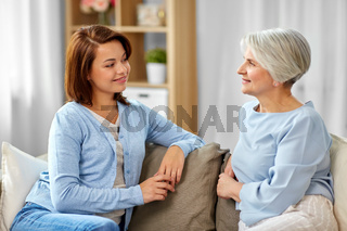 senior mother talking to adult daughter at home