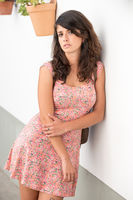 Serious young woman with a pink dress posing resting on a white wall in Badajoz, Extremadura, Spain.