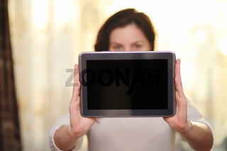 The girl is holding a tablet. The girl has a computer with a scr