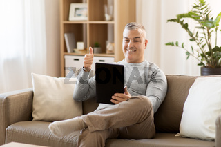 man having video chat on tablet pc at home