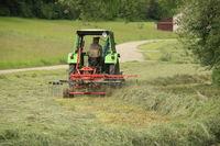 Landwirt mit Traktor und Heuwender bei der Heuernte