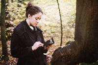 young woman using mobile smart phone outdoors in forest