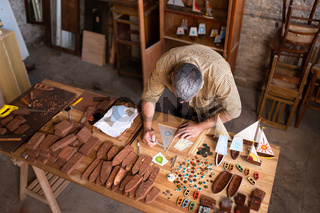 A joiner is sketching a model in his workshop