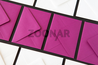 Composition with white and purple envelopes on the table.