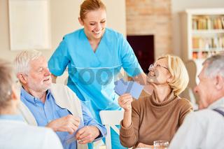 Lächelnde Pflegekraft schaut zu beim Kartenspiel