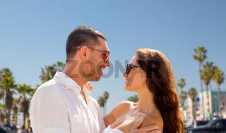happy couple in sunglasses over venice beach