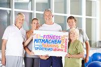 Senioren halten Plakat im Fitnesscenter