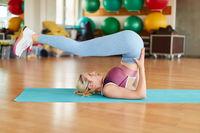 Frau macht einen Schulterstand im Yoga Kurs