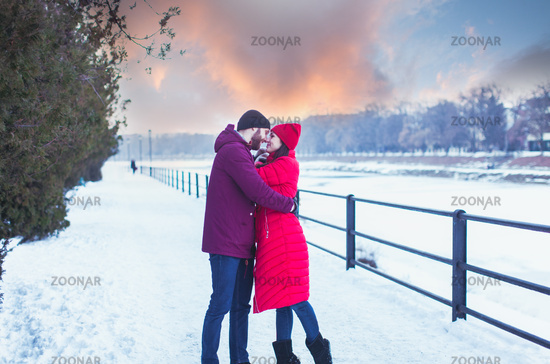 Young couple embracing during winter walk in city