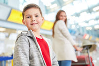 Junge und Mutter im Flughafen Terminal