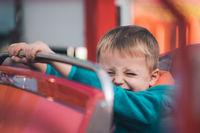Little boy in a carousel car
