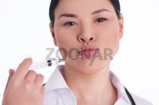 Nurse bringing syringe to her lips.