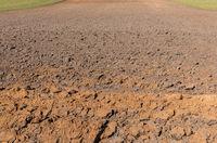 Plowed field in spring time, farm soil background