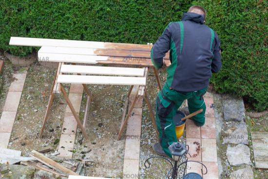 Man strokes protective paint on wooden garden furniture.