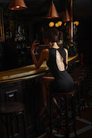 elegant lady in black dress, in restaurant at a bar