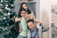 Family gather near Christmas tree