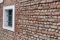 Schrägansicht einer Wand aus Backsteinen und Flusssteinen mit Fenster