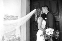 The Kiss. Bride and groom kisses tenderly in front of church portal.