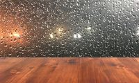 old brown oak wood table on the blurry drop on window background, wooden table.