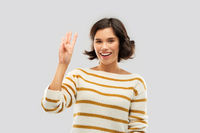 happy smiling woman showing four fingers