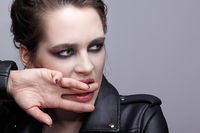 Portrait of female in black leather jacket bites finger. Woman with unusual beauty evening makeup and violet - black shadows make-up.