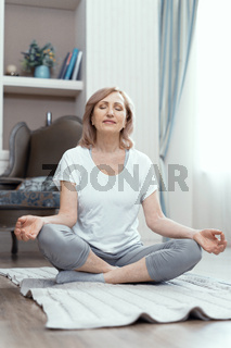 Woman is sitting with crossed legs. Yoga pose.
