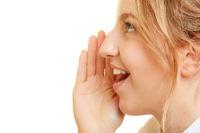 Frau flüstert leise Geheimnis mit Hand am Mund