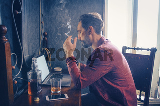 Handsome man works on his laptop smoking and drinking