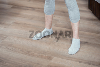 Female legs in gray socks on wooden floor. Closeup