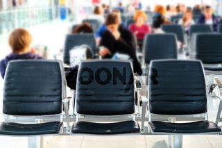 Airport lounge empty chairs. Blurred people waiting