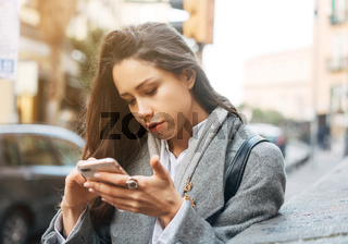 Woman using her mobile phone in the street.