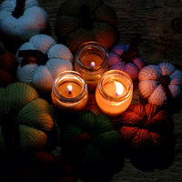 knitted pumpkin with candles in night