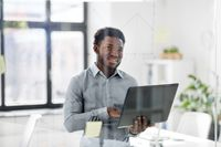 businessman with laptop at office glass board