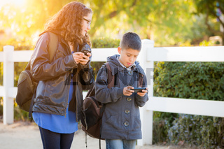 Hispanic Brother and Sister Wearing Backpacks Walking Texting On Cell Pones
