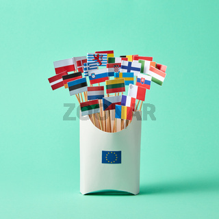 Set of different paper flags in cardboard box decorated with EU sign on green background with copy space. Economic, Political Union of European States