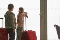Zwei Kinder im Flughafen Terminal schauen auf Startbahn