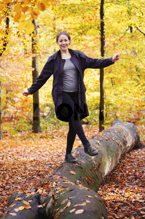 young woman balancing on tree trunk in forest in fall