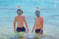 Two dutch men wearing snorkel masks in sea