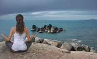 Young woman meditating outdoor at the sea coast with moody clody sky. Rear view