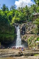 Tourists swim in the Tegenungan waterfall in Ubud, Bali, Indonesia