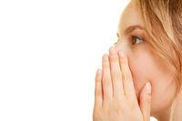 Frau hält Hand an Mund beim Flüstern