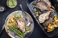Exotically barbecue veal back racks carree roast with green asaparagus and pineapple as top view in a backing dish