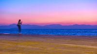 Sunset over Aegean Sea in Aegina Island and a girl on the wharf