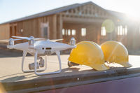 Drone Quadcopter Next to Hard Hat Helmets At Construction Site